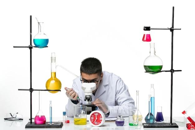 Widok z przodu męski chemik w białym kombinezonie medycznym pracujący z mikroskopem na białym tle wirus science covid- laboratorium pandemiczne