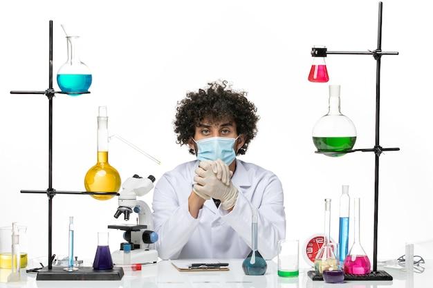 Widok z przodu męski chemik w garniturze medycznym iz maską po prostu siedzący z roztworami na białej przestrzeni