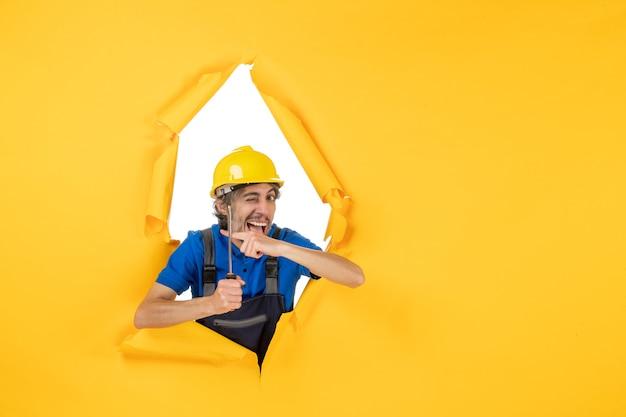 Widok z przodu męski konstruktor w mundurze ze śrubokrętem na żółtej ścianie praca konstruktor budynek kolor praca pracownik architektura