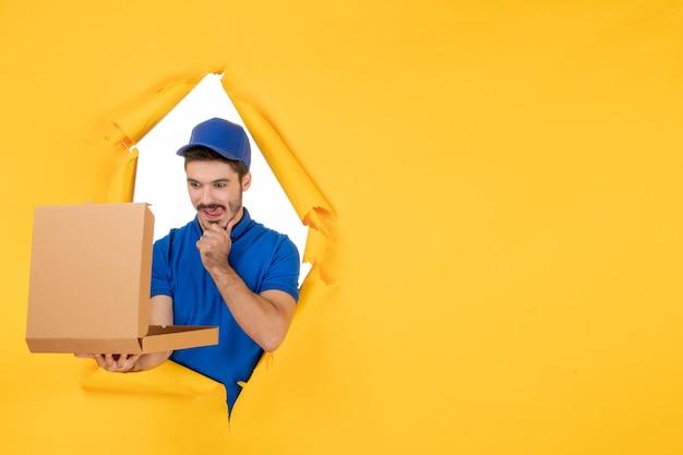 Widok z przodu męski kurier otwierający pudełko po pizzy na żółtej przestrzeni