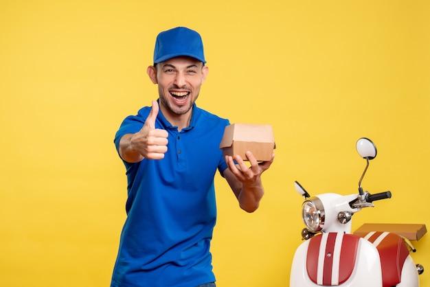 Widok z przodu męski kurier trzymający mały pakiet żywności na żółtym mundurze służbowym na rowerze pracownik dostawy pracy kolor