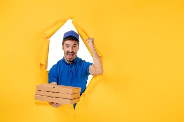Widok z przodu męski kurier trzymający pudełka po pizzy na żółtej podłodze kolor pracownik dostawa praca usługa jedzenie mundur praca