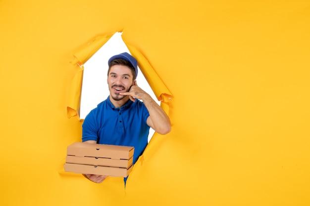 Widok z przodu męski kurier trzymający pudełka po pizzy na żółtej przestrzeni