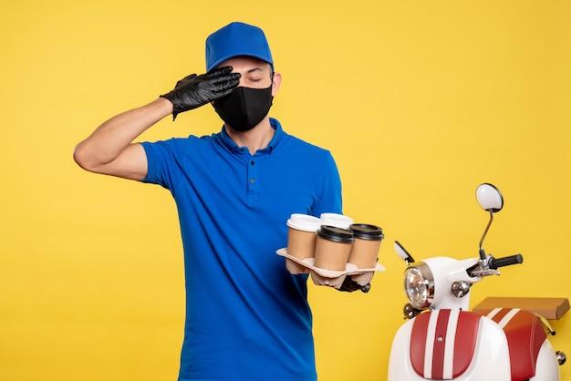 Widok z przodu męski kurier w czarnej masce trzymający kawę na żółtym zleceniu covid - mundur dostarczania usług pandemicznych