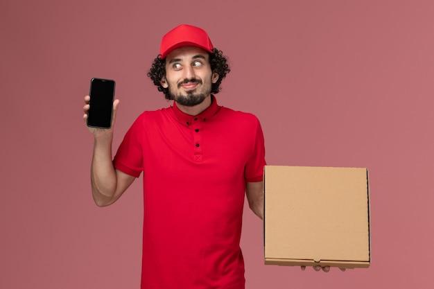 Widok z przodu męski kurier w czerwonej koszuli i pelerynie, trzymając puste pudełko na żywność z telefonem na różowej ścianie