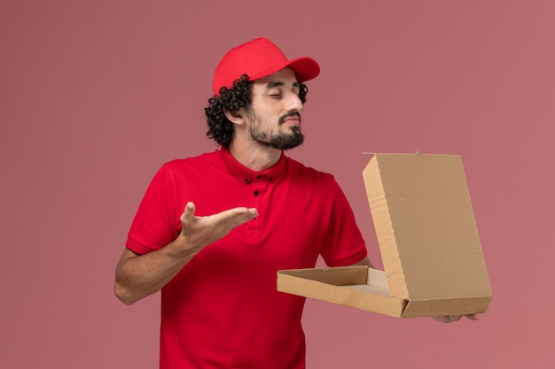 Widok z przodu męski kurier w czerwonej koszuli i pelerynie trzymający puste pudełko dostawy żywności pachnące na różowej ścianie