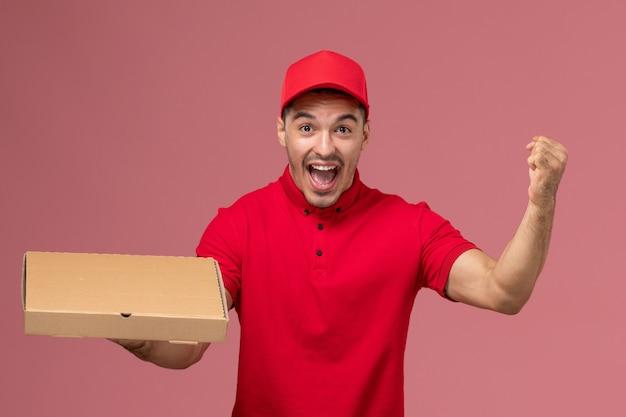 Widok z przodu męski kurier w czerwonym mundurze i pelerynie raduje się i trzyma pudełko z dostawą żywności na różowej ścianie pracownika pracy