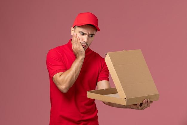Widok z przodu męski kurier w czerwonym mundurze i pelerynie, trzymając pudełko z jedzeniem, otwierając go na różowym pracownik biurowy