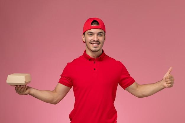 Widok z przodu męski kurier w czerwonym mundurze i pelerynie trzymający małą paczkę z dostawą uśmiechnięty na różowym tle.