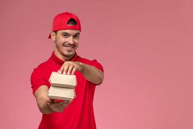 Widok z przodu męski kurier w czerwonym mundurze i pelerynie trzymający małe paczki z dostawą uśmiechnięty na różowym tle.