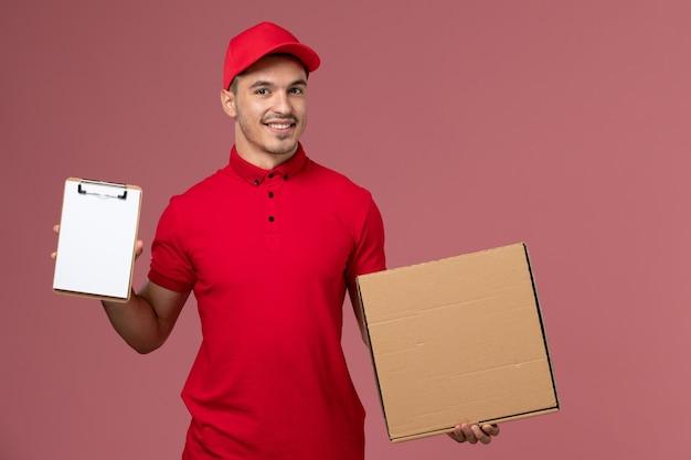 Widok z przodu męski kurier w czerwonym mundurze i pelerynie trzymający notatnik pudełko z jedzeniem na różowej ścianie praca serwisowa męski mundur dostawy