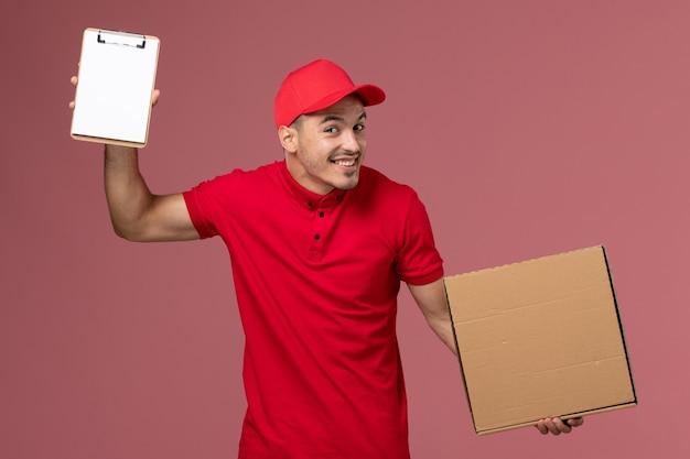 Widok z przodu męski kurier w czerwonym mundurze i pelerynie trzymający notatnik pudełko z jedzeniem z uśmiechem na różowej ścianie praca serwisowa męski mundur dostawy
