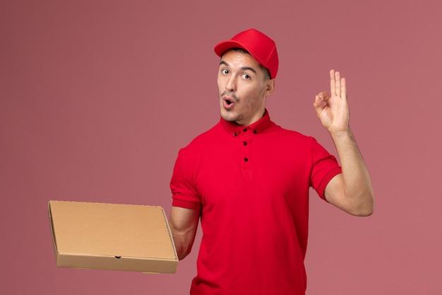 Widok z przodu męski kurier w czerwonym mundurze i pelerynie trzymający pudełko z dostawą żywności na jasnoróżowej pracy pracownika ściany