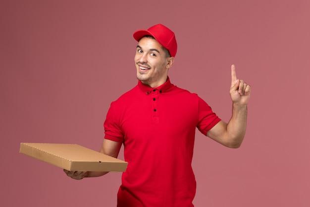 Widok z przodu męski kurier w czerwonym mundurze i pelerynie trzymający pudełko z dostawą żywności na różowej ścianie