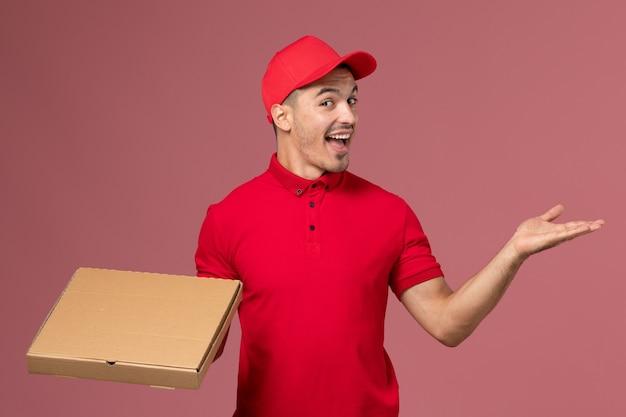 Widok z przodu męski kurier w czerwonym mundurze i pelerynie trzymający pudełko z dostawą żywności radujący się na różowej ścianie pracownika pracy