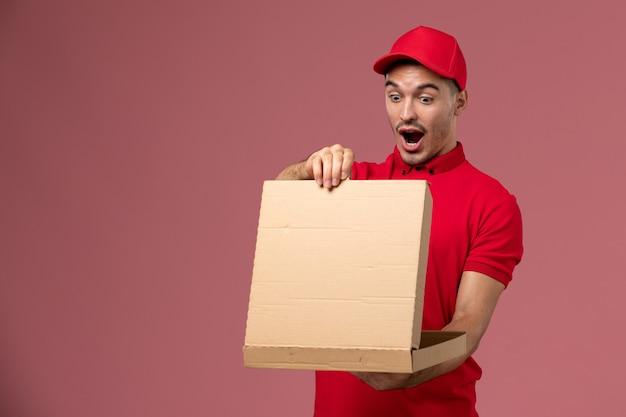 Widok z przodu męski kurier w czerwonym mundurze i pelerynie trzymający pudełko z jedzeniem otwierając go na jasnoróżowej pracy pracownika ściany