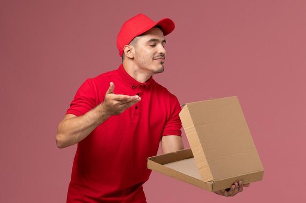 Widok z przodu męski kurier w czerwonym mundurze i pelerynie trzymający puste pudełko z jedzeniem na różowej ścianie praca serwisowa męski mundur dostawy