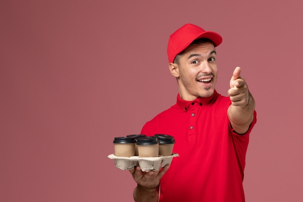 Widok z przodu męski kurier w czerwonym mundurze, trzymając brązowe filiżanki kawy dostawy na różowej ścianie
