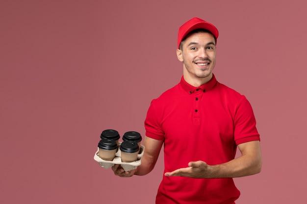 Widok z przodu męski kurier w czerwonym mundurze, trzymając brązowe filiżanki kawy dostawy z uśmiechem na różowej ścianie pracownika