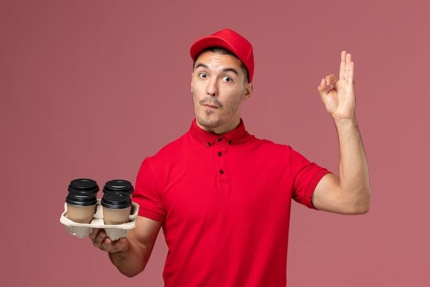 Widok z przodu męski kurier w czerwonym mundurze, trzymający brązowe filiżanki kawy dostawy na jasnoróżowym pracowniku ściany