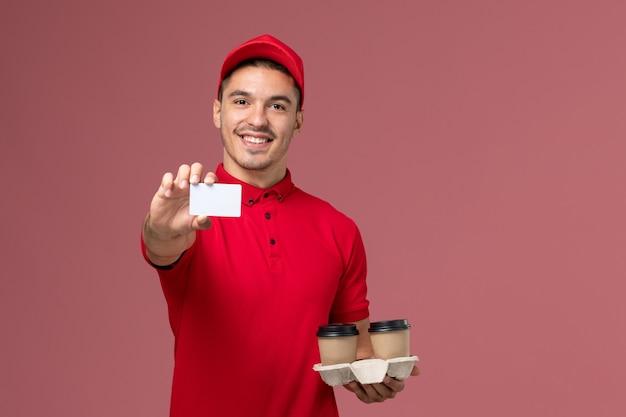 Widok z przodu męski kurier w czerwonym mundurze, trzymający brązowe filiżanki z kawą z białą kartą na jasnoróżowej ścianie