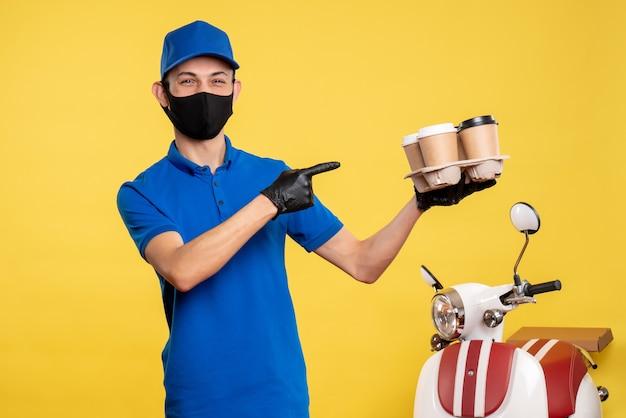 Widok z przodu męski kurier w masce trzymający kawę na żółtym mundurze roboczym covid - usługa pandemii dostawy