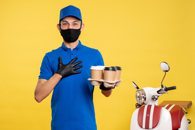 Widok z przodu męski kurier w masce z kawą dostawczą na żółtym pandemicznym zleceniu dostawy covid - jednolita praca służbowa