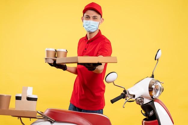 Widok z przodu męski kurier w mundurze z pudełkiem na kawę i jedzenie na żółtej pandemii pracy usługowej w jednolitym kolorze
