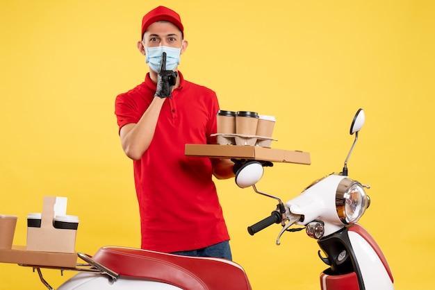 Widok z przodu męski kurier w mundurze z pudełkiem z kawą i jedzeniem na żółtej usłudze pandemicznej w pracy z kolorowym wirusem pracy