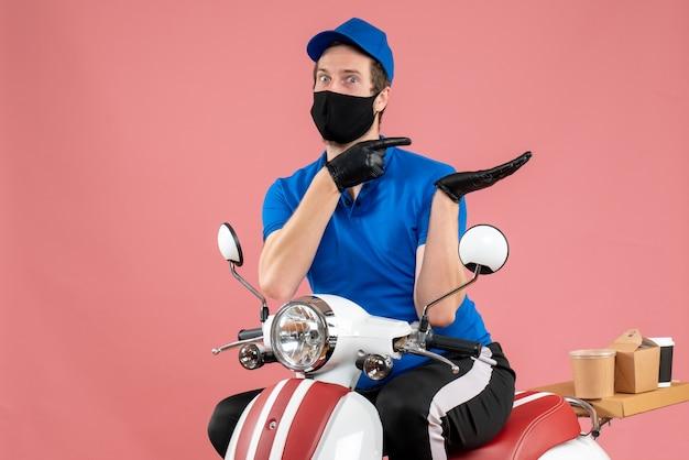 Widok z przodu męski kurier w niebieskim mundurze i masce na różowym serwisie wirusowym na rowerze fast-food covid-dostawa!