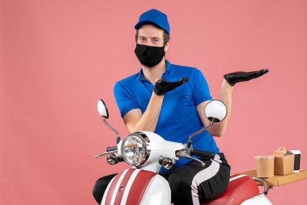 Widok z przodu męski kurier w niebieskim mundurze i masce na różowym serwisie wirusowym na rowerze fast-food covid-work work