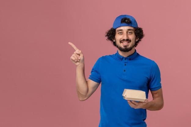 Widok z przodu męski kurier w niebieskim mundurze i pelerynie trzymający małą paczkę z dostawą żywności na różowej ścianie