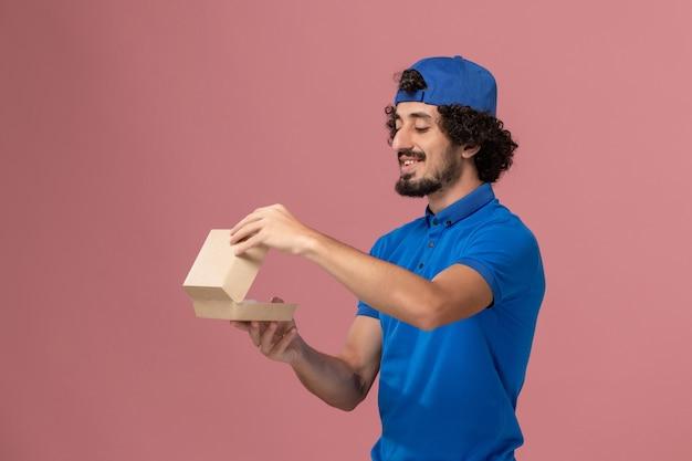 Widok z przodu męski kurier w niebieskim mundurze i pelerynie trzymający małą paczkę z dostawą żywności otwierającą ją na różowej ścianie