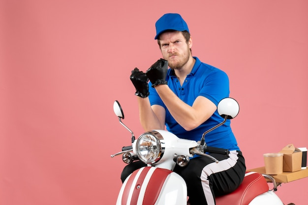 Widok z przodu męski kurier w niebieskim mundurze na różowym jedzeniu rower dostawa praca kolor praca usługa fast-food