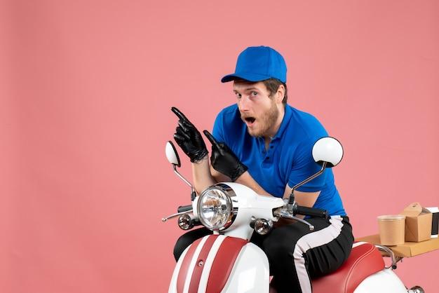 Widok z przodu męski kurier w niebieskim mundurze na różowym kolorze praca fast-food bike service food job delivery