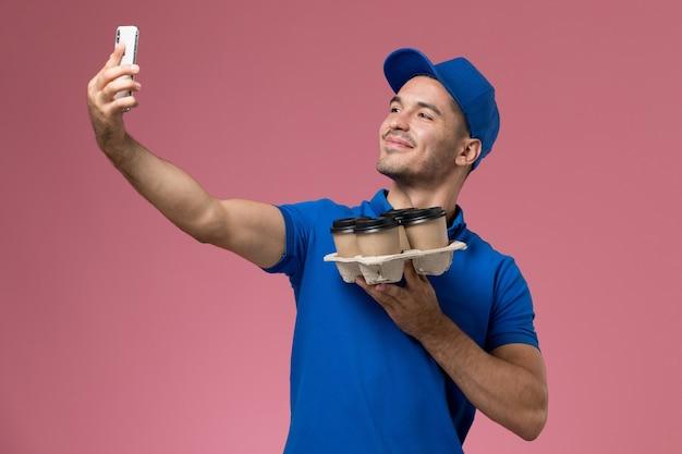 Widok z przodu męski kurier w niebieskim mundurze robi selfie z dostawą filiżanek na różowej ścianie, jednolita dostawa usług pracownika