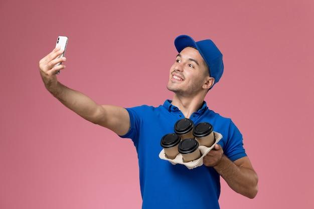 Widok z przodu męski kurier w niebieskim mundurze robiący selfie z kawą na różowej ścianie, jednolita dostawa pracy serwisowej
