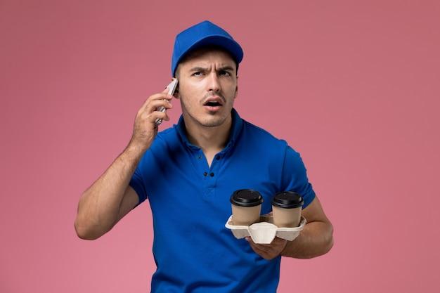 Widok z przodu męski kurier w niebieskim mundurze rozmawiający przez telefon i trzymający filiżanki z kawą na różowej ścianie, jednolita dostawa pracy serwisowej