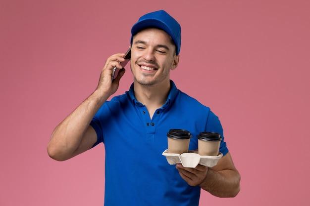 Widok z przodu męski kurier w niebieskim mundurze rozmawiający przez telefon trzymający filiżanki z kawą na różowej ścianie, jednolita dostawa zlecenia serwisowego