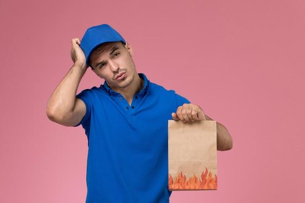 Widok z przodu męski kurier w niebieskim mundurze, trzymając pakiet papieru z żywnością na różowej ścianie, jednolita dostawa usług pracownika