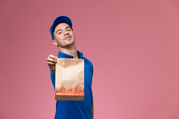 Widok z przodu męski kurier w niebieskim mundurze, trzymając pakiet żywności na różowej ścianie, dostawa usług munduru pracownika