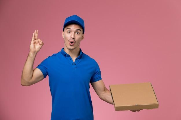 Widok z przodu męski kurier w niebieskim mundurze, trzymając pudełko z jedzeniem pozuje na różowej ścianie, dostawa usług mundurowych pracownika