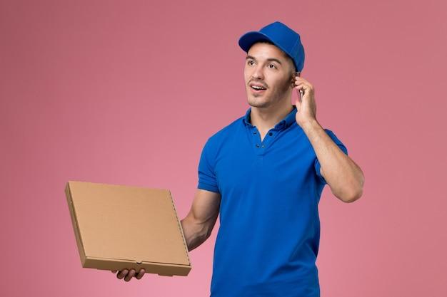 Widok z przodu męski kurier w niebieskim mundurze, trzymając pudełko z jedzeniem, rozmawiając przez telefon na różowej ścianie, jednolita dostawa pracy serwisowej