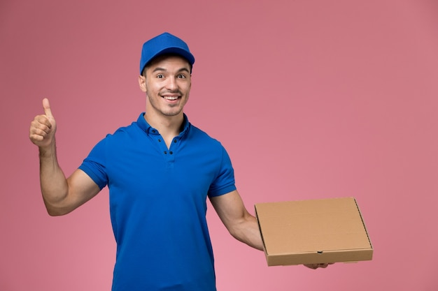 Widok z przodu męski kurier w niebieskim mundurze, trzymając pudełko z jedzeniem z uśmiechem na różowej ścianie, jednolita dostawa pracy serwisowej