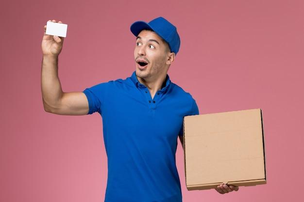 Widok z przodu męski kurier w niebieskim mundurze, trzymający białą kartkę z pudełkiem na żywność na różowej ścianie, dostawa usług munduru pracownika