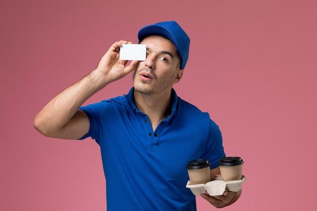 Widok z przodu męski kurier w niebieskim mundurze trzymający filiżanki kawy z białymi kartami na różowej ścianie, dostawa usług mundurowych pracownika