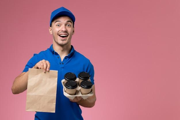 Widok z przodu męski kurier w niebieskim mundurze trzymający opakowanie żywności i kawę na różowej ścianie, jednolita dostawa pracy serwisowej