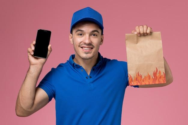 Widok z przodu męski kurier w niebieskim mundurze trzymający paczkę z jedzeniem i telefon na różowej ścianie, jednolita dostawa usług