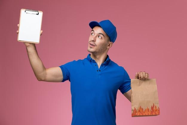 Widok z przodu męski kurier w niebieskim mundurze trzymający pakiet papieru z żywnością i notatnik na różowej ścianie, jednolita dostawa pracy serwisowej