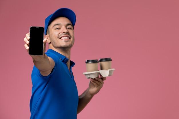 Widok z przodu męski kurier w niebieskim mundurze trzymający telefon i filiżanki z kawą na różowej ścianie, jednolita dostawa pracy serwisowej